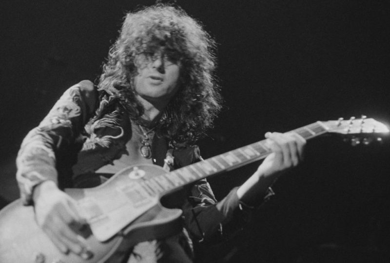 Guitarist Jimmy Page performing with British heavy rock group Led Zeppelin, at Earl's Court, London, May 1975. The band were initially booked to play three nights at the venue, from 23rd to 25th May, but due to public demand, two more concerts were later added, for 17th and 18th May. Total ticket sales were 85,000. (Photo by Michael Putland/Getty Images)