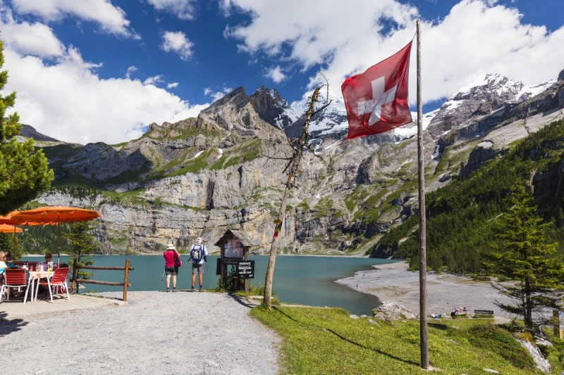 Hiker standing by Swiss national flagg in front of Lake Oeschinensee, UNESCO World Heritage Site, Bernese Oberland