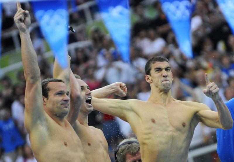 US swimmers Michael Phelps (R), Aaron Peirsol (C) and Brendan Hansen (L) react during the men's 4 x 100m medley relay swimming final at the National Aquatics Center during the 2008 Beijing Olympic Games in Beijing on August 17, 2008. Michael Phelps became the first man to win eight gold medals at the same Olympics when the US won the men's 4x100m medley relay final in a new world record time. AFP PHOTO / TIMOTHY CLARY (Photo credit should read TIMOTHY CLARY/AFP/Getty Images)