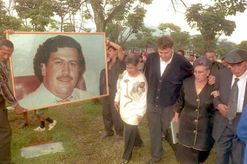 Hermilda de Escobar (2nd-R), mother of Medellin drug cartel kingpin Pablo Escobar (portrait), walks with friends and relatives to Escobar's tomb to celebrate the first anniversary of his death. Escobar was killed by Colombian special forces after being discovered hiding in a house in Medellin. (COLOR KEY: Trees are green.) (Photo credit should read GUILLERMO TAPIA/AFP/Getty Images)