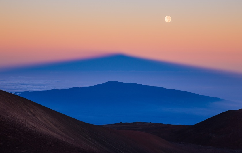 The shadow of Manua Kea, the highest peak in the state of Hawaii, is projected by the rising sun over the volcano, Hualalai, whilst the Full Moon soars above them, higher again. (Sean Goebel)
