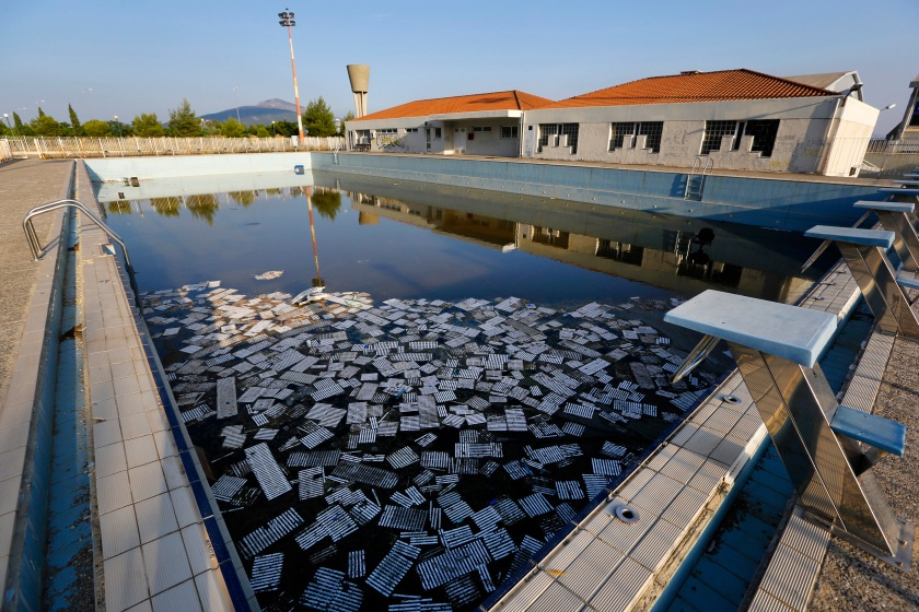 Garbage floats in a deserted swimming pool at the Olympic Village in Thrakomakedones, north of Athens July 25, 2014. Ten years after Greece hosted the world's greatest sporting extravaganza, many of its once-gleaming Olympic venues have been abandoned while others are used occasionally for non-sporting events such as conferences and weddings. For many Greeks who swelled with pride at the time, the Olympics are now a source of anger as the country struggles through a six-year depression, record unemployment, homelessness and poverty. Just days before the anniversary of the Aug. 13-29 Games in 2004, many question how Greece, among the smallest countries to ever host the Games, has benefited from the multi-billion dollar event. Picture taken July 25, 2014. REUTERS/Yannis Behrakis (GREECE - Tags: SOCIETY SPORT POLITICS BUSINESS) ATTENTION EDITORS: PICTURE 21 OF 33 FOR WIDER IMAGE PACKAGE 'TEN YEARS ON - ATHENS' FADING OLYMPIC STADIUMS' TO FIND ALL IMAGES SEARCH 'BEHRAKIS KARAHALIS' - RTR41JQL