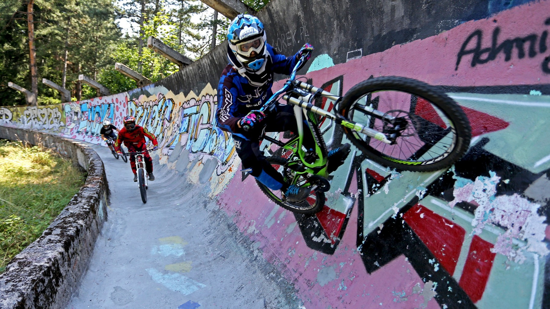Downhill bikers Kemal Mulic (C), Tarik Hadzic (L) and Kamer Kolar train on the disused bobsled track from the 1984 Sarajevo Winter Olympics on Trebevic mountain near Sarajevo, Bosnia and Herzegovina, August 8, 2015. Abandoned and left to crumble into oblivion, most of the 1984 Winter Olympic venues in Bosnia's capital Sarajevo have been reduced to rubble by neglect as much as the 1990s conflict that tore apart the former Yugoslavia. The bobsled and luge track at Mount Trebevic, the Mount Igman ski jumping course and accompanying infrastructure are now decomposing into obscurity. The bobsled and luge track, which was also used for World Cup competitions after the Olympics, became a Bosnian-Serb artillery stronghold during the war and is nowadays a target of frequent vandalism. Picture taken August 8. REUTERS/Dado Ruvic      TPX IMAGES OF THE DAY      - RTX1NQ1L