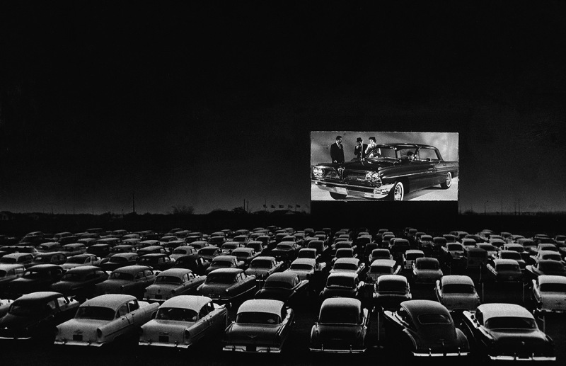 Vehicles fill a drive-in theater while people on the screen stand near a new car, 1950s. (Photo by New York Times Co./Hulton Archive/Getty Images)