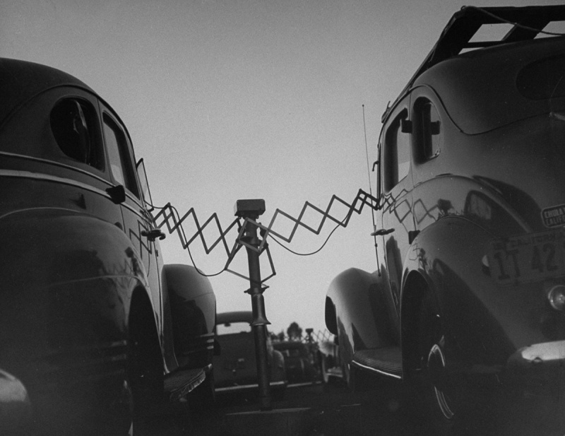 Cars parked at Rancho Drive-In Theater w. the accordion-like fulcrum arms of movie speakers reaching into each driver's front window, which they will push back onto the central post when the movie is over. (Photo by Allan Grant/The LIFE Picture Collection/Getty Images)