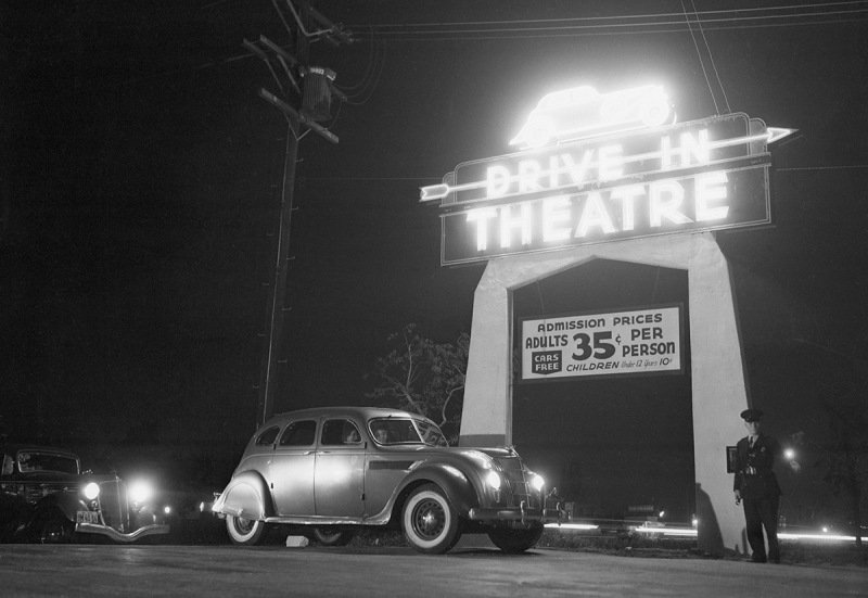 5/21/1938-Los Angeles, CA-ORIGINAL CAPTION READS: Motoring and motion pictures achieve a happy wedding in the Drive-In Theater of Los Angeles. The theater is a parking lot with graduated tiers from which motorists, seated in their own cars, watch the films projected on a giant screen. Synchronized amplifiers in front of each automobile make speech audible in all parts of the lot. Here's a view of the entrance to the theater with customers about to drive in.