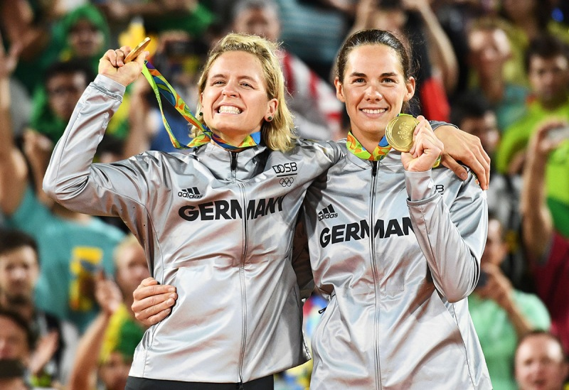 Germany's gold medallists, Laura Ludwig (L) and Kira Walkenhorst, celebrate on the podium at the end of the women's beach volleyball event. (Leon Neal/AFP/Getty Images)