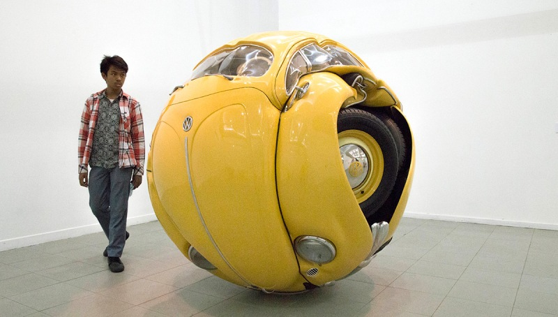"""A student visitor looking at """"beetle sphere"""" sculpture by sculptor Ichwan Noor. Indonesia National Gallery held it 2nd Sculptor exhibition from selected sculptor arround Indonesia called """"Trienal Sculpture Art Exhibition"""" with theme """"Versi"""" (version) based on two strong paradigm in Sculpture art : respecting the tradition on human craft and using experimental base on deep though and concept. The exhibition is the second time exhibition at the gallery. (Photo by Donal Husni/NurPhoto) (Photo by NurPhoto/NurPhoto via Getty Images)"""