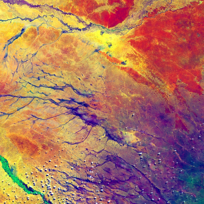 The deep purple in the lower right spreads out into a few channels before fading into a multitude of colors. These channels are remnants of an ancient drainage network in Kenya. The beauty of the colors actually hides a stark reality for hundreds of thousands of people. The dark spots at the top center of the image are refugee camps (USGS/NASA)