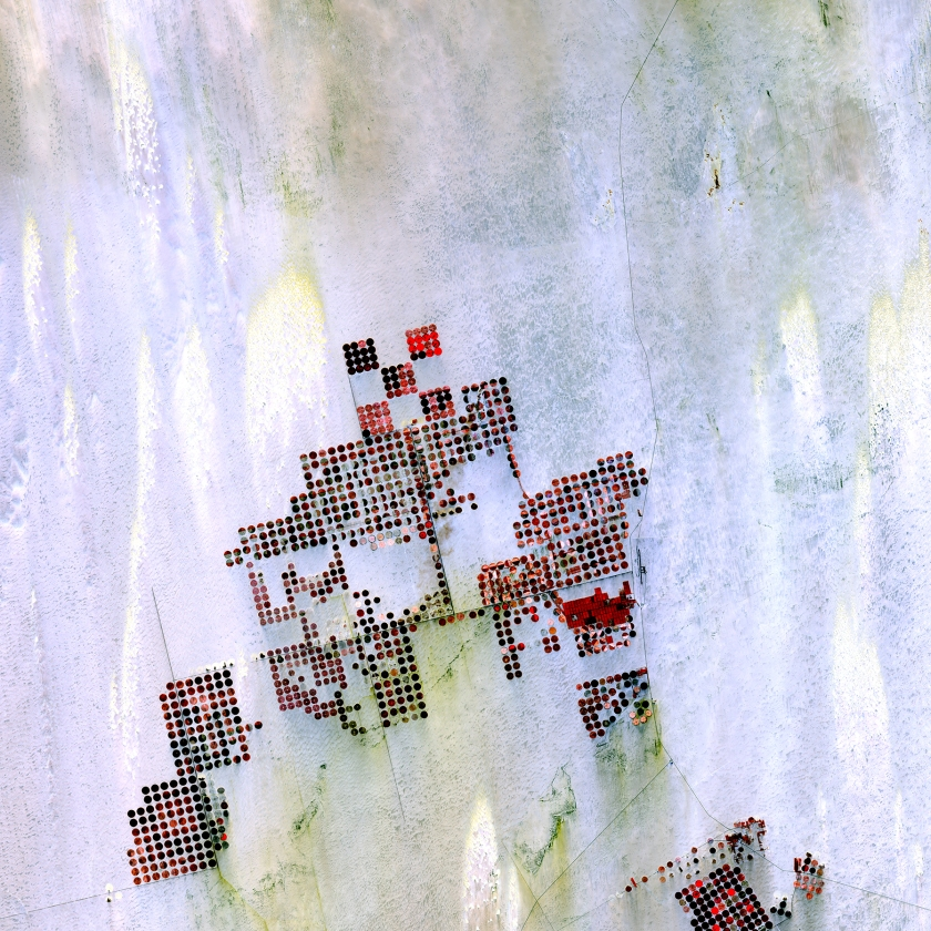 Geometric shapes lie across the emptiness of the Sahara Desert in southern Egypt. Each point is a center pivot irrigation field a little less than 1 kilometer (0.6 mile) across. With no surface water in this region, wells pump underground water to rotating sprinklers from the huge Nubian Sandstone aquifer, which lies underneath the desert. (USGS/NASA)