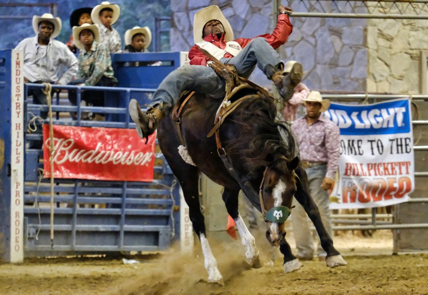 """Tre Hosley competes in a bareback riding event at the Bill Pickett Invitational Rodeo in Industry, Calif., on Saturday, June 16, 2016. """"Gangsters turn into little kids when they see a horse,"""" says the Compton, Calif. resident, recalling how he once rode one into the wrong neighborhood and was confronted by a handful of gang members who wanted to play with the horse. (AP Photo/Richard Vogel)"""