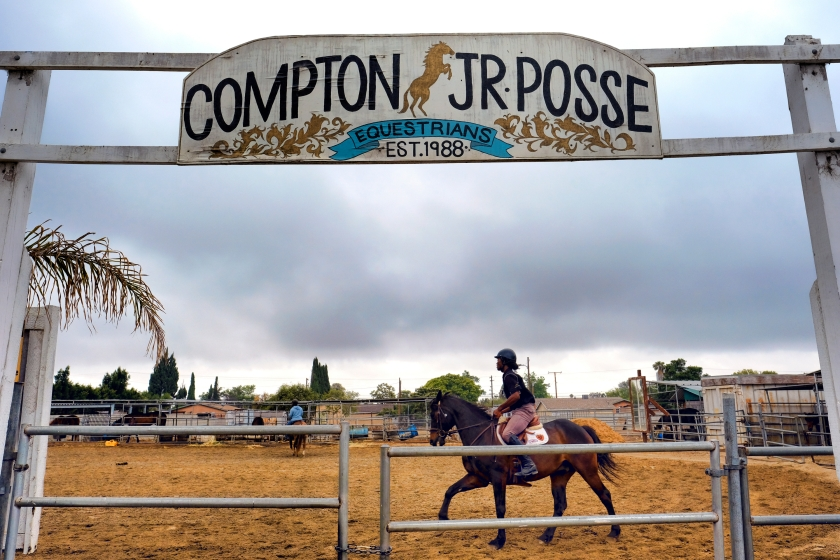 Nathon Bonner warms up one of the horses in the Compton Junior Posse Youth Equestrian Program in Compton, Calif., on Saturday, June 6, 2016. Hundreds of people keep horses in their backyards in its agriculturally-zoned Richland Farms neighborhood and ride them on the streets around town, as well as at rodeos and other equestrian competitions across the country. (AP Photo/Richard Vogel)