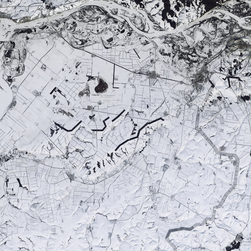 Is this a black-and-white image? No, this is a natural color image of snow-covered southwestern Russia. Windbreaks, roads, and fence lines look like random pencil marks near the Volga River, which flows across the top of the image. The thick lines are trees planted to protect fields from dry wind and erosion; these windbreaks retain snow, allowing more moisture to penetrate into the soil. (USGS/NASA)