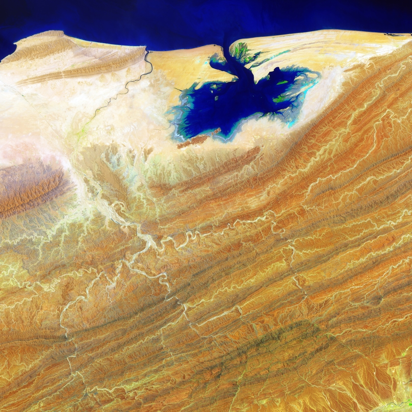 Like blue ink bleeding onto parchment, the Khor Kalmat lagoon branches off the Arabian Sea and spills into the southern Pakistan landscape near the Makran Coast Range. Mudflats cover almost the entire lagoon, which fills with shallow water at high tides. The small areas of green are isolated pockets of mangrove forest. (USGS/NASA)