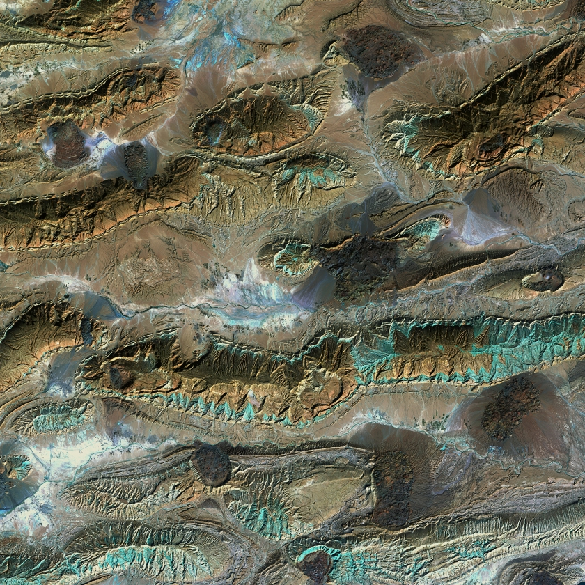 The patterns and colors in the Zagros Mountains of Iran are interesting enough. For example, the infrared view provides a patina-like outline to the mountains. But something more happened to this unique landscape. Interrupting the mountain patterns are irregular dark patches called salt glaciers. What began as salt domes buried under the rock pushed up through the Earth, squeezing to the surface like toothpaste.(USGS/NASA)