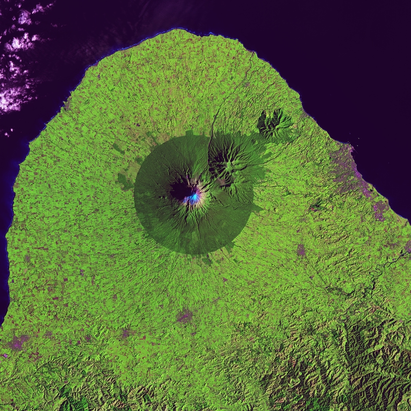 A nearly perfect circle of forest delineates the boundary of Egmont National Park in New Zealand. Snow-capped Mount Taranaki marks the center of the park, which is surrounded by green farmland. (USGS/NASA)