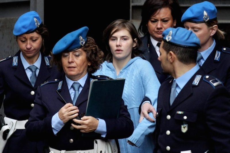 PERUGIA, ITALY - NOVEMBER 24: Amanda Knox (C) is led away from Perugia's Court of Appeal by police officers after the first session of her appeal against her murder conviction on November 24, 2010 in Perugia, Italy. American Amanda Knox and her Italian ex-boyfriend Raffaele Sollecito were convicted of the murder of Ms Knox's former British flatmate Meredith Kercher in 2007. Their initial trial completed in December 2009 with Knox and Sollecito receiving sentences of 26 and 25 years respectively. Rudy Guede, an unemployed man from Ivory Coast, was also convicted of the murder of Meredith Kercher. The case is also forming the basis for a film currently being shot in Italy entitled 'The Amanda Knox Story', with American actress Hayden Panettiere cast as Amanda Knox. (Photo by Oli Scarff/Getty Images)