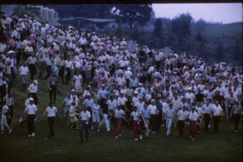 """LIGONIER, PA - AUGUST 1965: Arnold Palmer walks the course followed by """"Arnie's Army"""" during the 1965 PGA Championship at Laurel Valley Golf Club in August 1965 in Ligonier, Pennsylvania. (Photo by Robert Riger/Getty Images)"""