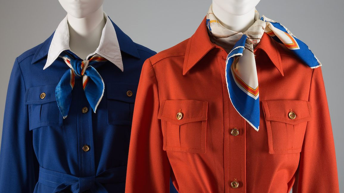 Cobalt blue TWA uniform; jacket, skirt & belt in wool; shirt style jacket with tie belt; A-line skirt with stitched & released pleats at front TWA uniform; jacket, belt, pants in wool; orange shirt style jacket with tie belt; beige wide leg pants with woven stripe in red, blue & yellow