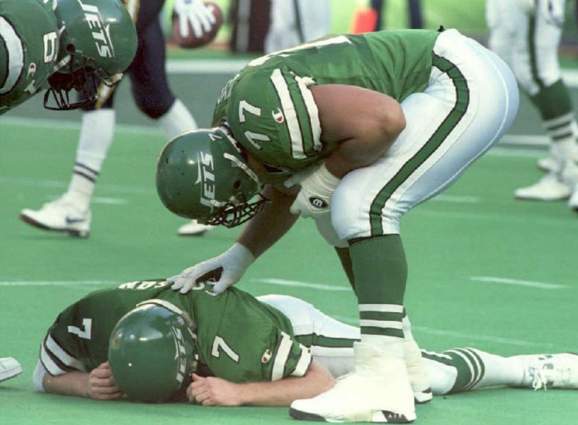 New York Jets' Matt Willig (R) and Dwayne White (L) check on their quarterback Boomer Esiason who was knocked down, and suffered a concussion, after throwing an incomplete pass in the second quarter at Giants Stadium 18 December 1994. Esiason had to leave the game and was replaced by Jack Trudeau. (Henny Ray Abrams/AFP/Getty Images)