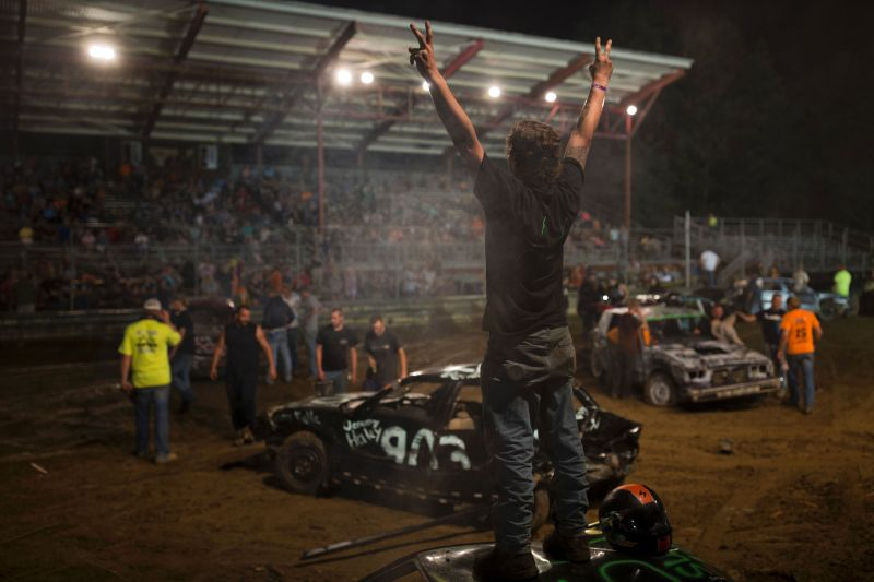 A driver gestures toward the crowd after a heat in the annual demolition derby at the Cambria County Fair on September 8, 2016, in Ebensburg, Pennsylvania. / AFP / DOMINICK REUTER (Photo credit should read DOMINICK REUTER/AFP/Getty Images)