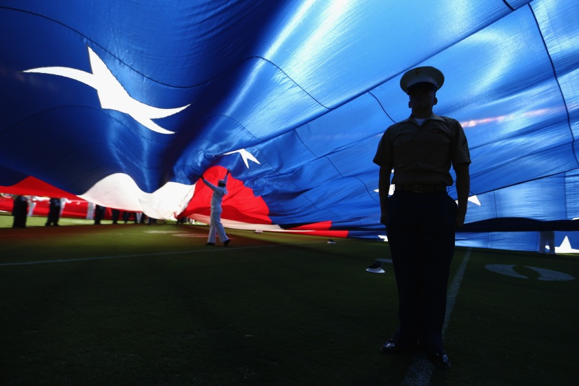 A U.S. Marine stands at attention under a large American flag before a game between the Jacksonville Jaguars and the San Diego Chargers at Qualcomm Stadium on September 18, 2016 in San Diego, California. (Sean M. Haffey/Getty Images)
