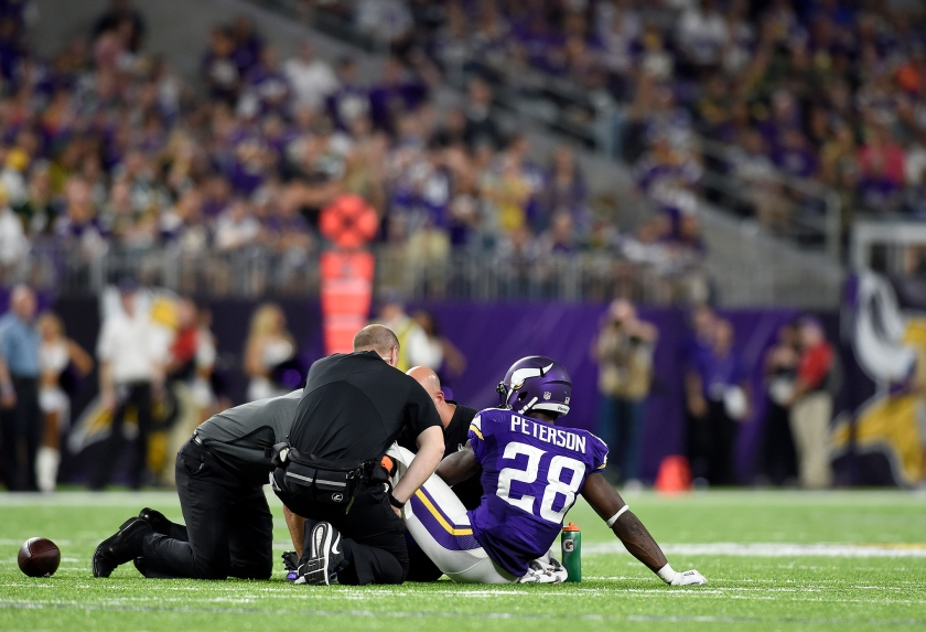 Adrian Peterson #28 of the Minnesota Vikings sits on the field as trainers tended to his knee in the third quarter of the game against the Green Bay Packers on September 18, 2016 at US Bank Stadium in Minneapolis, Minnesota. Peterson was carried to the sidelines and later went to the locker room. (Hannah Foslien/Getty Images)