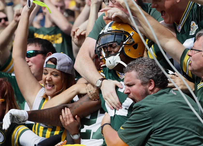 """Davante Adams #17 of the Green Bay Packers is grabbed by fans after a """"Lambeau Leap"""" following his touchdown catch in the first quarter against the Detroit Lions at Lambeau Field on September 25, 2016 in Green Bay, Wisconsin. (Jonathan Daniel/Getty Images)"""
