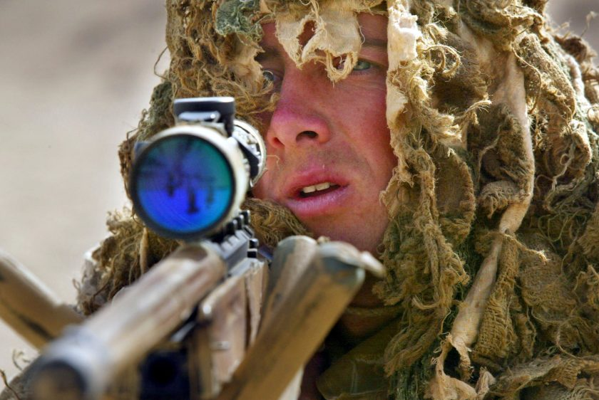 Marine Alasdair Kane, a British Royal Marine soldier from the 42nd Commando Lima Brigade, goes through training exercises in camouflage using a .338 sniper rifle March 10, 2003 in the desert 70 kilometers from Kuwait city near the Iraqi border. (Paula Bronstein/Getty Images)