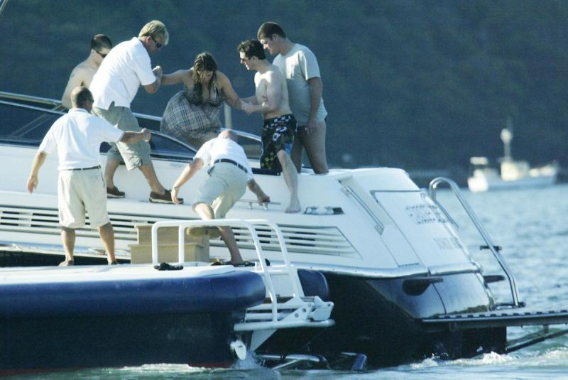 (AUSTRALIA & NEW ZEALAND OUT) Tom Cruise and James Packer help Cruise's pregnant girlfriend Katie Holmes aboard Packer's yacht Arctic P on Sydney Harbour, 18 February 2006. SHD Picture by ANDREW MEARES (Photo by Fairfax Media via Getty Images)