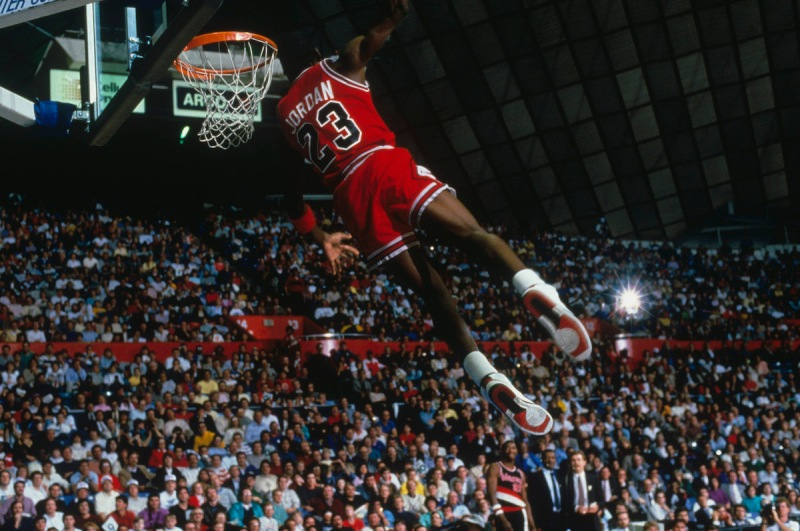 UNDATED: Chicago Bulls' forward Michael Jordan #23 jumps and dunks as the crowd takes photos during a game. NOTE TO USER: User expressly acknowledges and agrees that, by downloading and/or using this Photograph, user is consenting to the terms and conditions of the Getty Images License Agreement. (Photo by Focus on Sport/Getty Images) *** Local Caption *** Michael Jordan