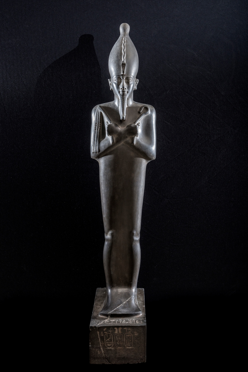 Standing image of Osiris wearing the white crown, uraei and r egalia (Grey-green Graywacke, H. 1.50 m). This masterpiece of Saite statuary carries a dedi cation from the ͞ divine adorer of Amun ͟ Nitocris, daughter of Psamtik I (664-610 BC).The look of the ͞ Lord of Life ͟ seems fixed on a point beyond space and time, and his entire bei ng radiates an intense energy of life. (Franck Goddio/Hilti Foundation)