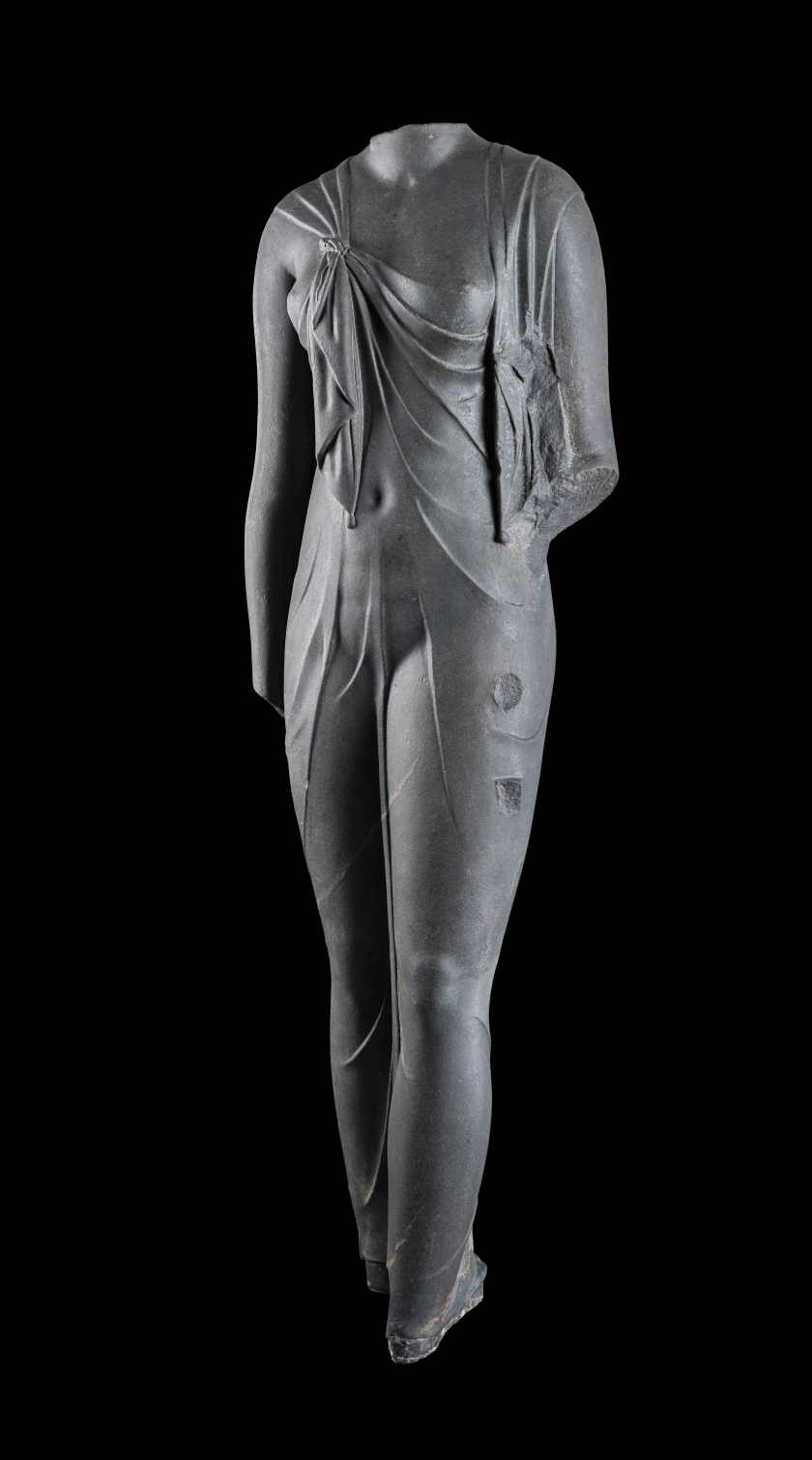 Cut in hard, dark stone, this feminine body has a startli ngly sculptural quality. Complete, it must have been slightly larger than life-size. The statu e is certainly one of the queens of the Ptolemaic dynasty (likely Arsinoe II) dressed as the goddes s Isis, as confirmed by the knot that joins the ends of the shawl the woman wears, w hich was representative of the queens during this time period. The statue was found at t he site of Canopus. (Franck Goddio/Hilti Foundation)