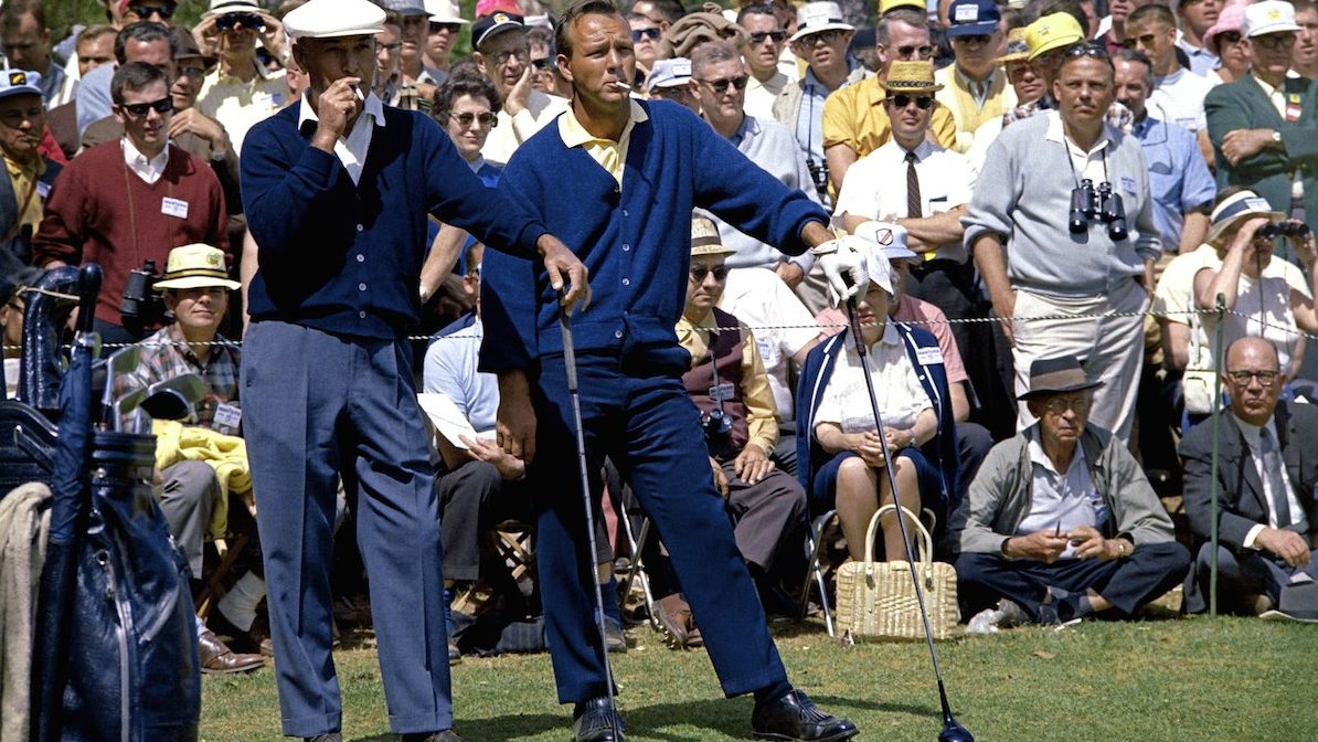 AUGUSTA, GA - APRIL 1966:  (L-R) Ben Hogan and Arnold Palmer smoke as they wait in front of a gallery to play their tee shot on the second hole during the 1966 Masters Tournament at Augusta National Golf Club held April 7-11, 1966 in Augusta, Georgia. (Photo by Augusta National/Getty Images)