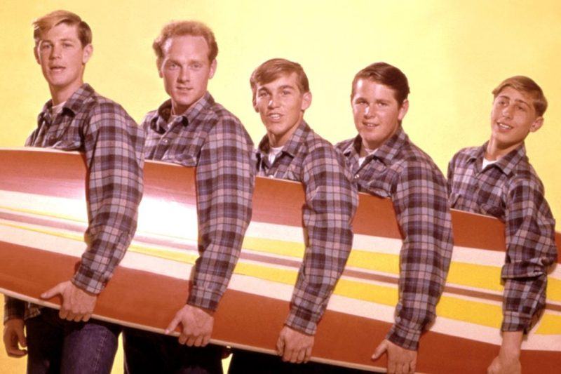 """LOS ANGELES - AUGUST 1962: Rock and roll band """"The Beach Boys"""" pose for a portrait with a surfboard in August 1962 in Los Angeles, California. (L-R) Brian Wilson, Mike Love, Dennis Wilson, Carl Wilson, David Marks. (Photo by Michael Ochs Archives/Getty Images)"""
