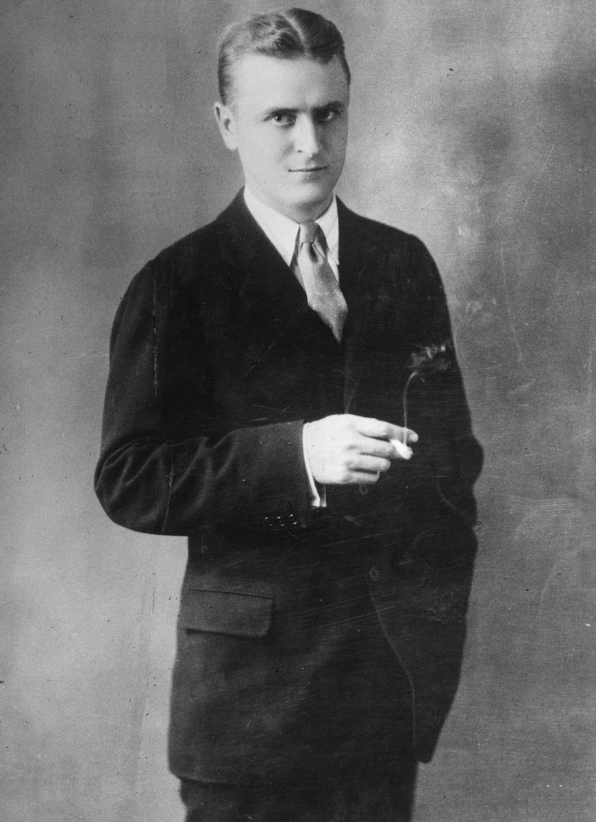 1925:  A studio portrait of American writer F. Scott Fitzgerald (1896 - 1940) wearing a suit and tie and holding a lighted cigarette.  (Photo by Hulton Archive/Getty Images)