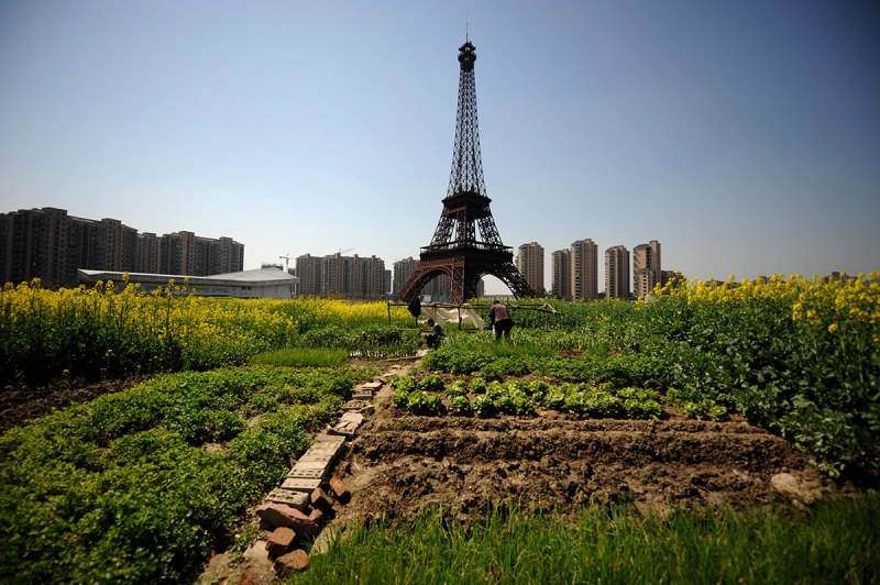 HANGZHOU, CHINA - MARCH 21: (CHINA OUT) Farmers work in front of a replica of The Eiffel Tower standing at 108 metres at Tianducheng residential community, also known as a knockoff of Paris, on March 21, 2014 in Hangzhou, China. Tianducheng is developed by Zhejiang Guangsha Co. Ltd.. The construction began in 2007 with a replica of the Eiffel Tower and Parisian houses, and it is expected to be completed by 2015. (Photo by VCG/VCG via Getty Images)