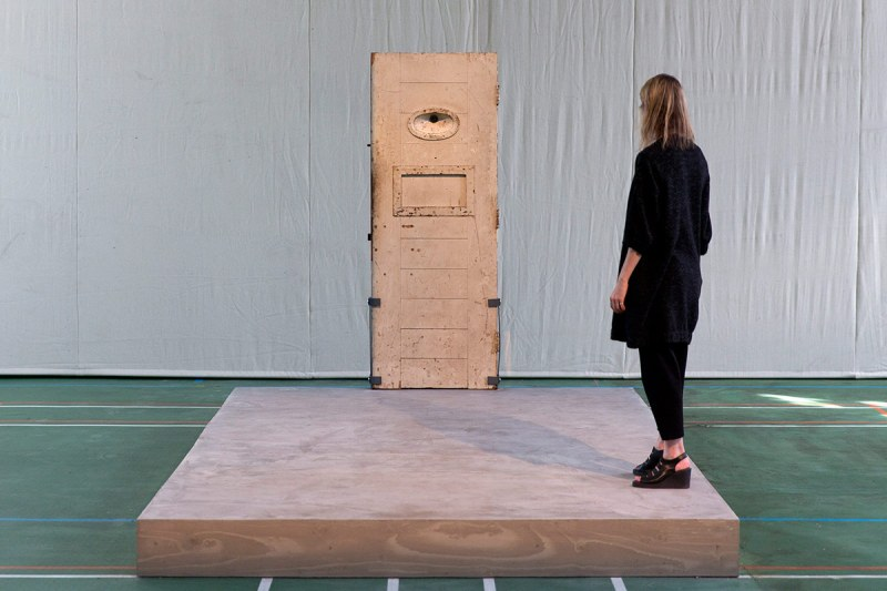 An assistant stands on an artwork by French artist Jean-Michel Pancin which replicates by way of the original door and exact dimensions the prison cell of author Oscar Wilde when he was incarcerated in Reading prison during an exhibition at the prison on September 1, 2016. Reading Prison will open to the public for a major new project in which leading artists, performers and writers respond to the work of the prison's most famous inmate Oscar Wilde. / AFP / JUSTIN TALLIS / RESTRICTED TO EDITORIAL USE - MANDATORY MENTION OF THE ARTIST UPON PUBLICATION - TO ILLUSTRATE THE EVENT AS SPECIFIED IN THE CAPTION (Photo credit should read JUSTIN TALLIS/AFP/Getty Images)