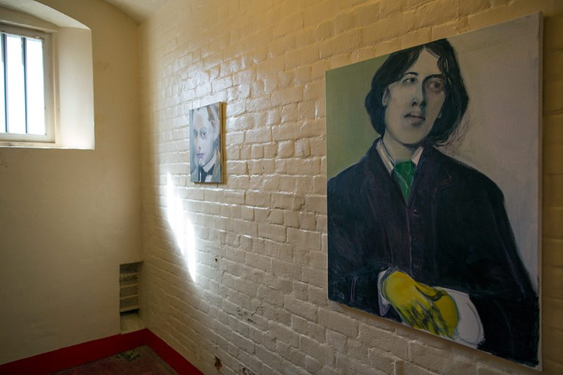 READING, ENGLAND - SEPTEMBER 01: A picture of Oscar Wilde hangs inside a cell inside the former Reading prison building on September 1, 2016 in Reading, England. The former Reading Prison has opened to the public for the first time, inviting artists and writers in to take part in a new project by Artangel, with works by leading artists including Marlene Dumas, Robert Gober, Nan Goldin, Steve McQueen, and Ai Weiwei. The exhibition opens to the public from September 4, 2016. Included in the exhibit is former inmate Oscar Wildes original wooden cell door, which is on display in the prison chapel. (Photo by Dan Kitwood/Getty Images)