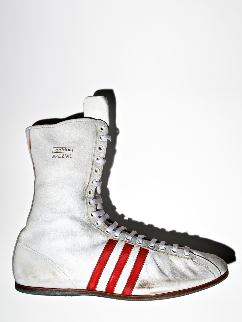 """American boxer Muhammad Ali's Adidas """"Special"""" boxing shoe, size 13 US. Made with kangaroo leather uppers, Ali received these shoes when he defended his WBC title against Karl Mildenberger on October 9th, 1966 in Frankfurt, Germany. Banned from boxing in 1968 for refusing to fight in Vietnam, Ali sent back another shoe — signed and dedicated to Adi Dassler, the founder of Adidas — because he thought he wouldn't need them anymore.(Henry Leutwyler)"""