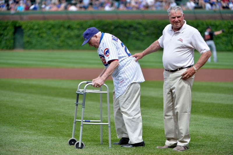 CHICAGO, IL - JUNE 7: Lennie Merullo (L), a member of the Chicago Cubs 1945 World Series team, is helped by his son Lennie Merullo Jr. as he walks onto the field to throw out a ceremonial first pitch before the Chicago Cubs Miami Marlins game at Wrigley Field June 7, 2014 in Chicago, Illinois. Merullo is the only surviving member of the Chicago Cubs who has ever played in a World Series game in a Cubs uniform. The Cubs defeated the Marlins 5-2. (Photo by Brian D. Kersey/Getty Images)