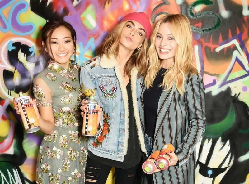 """LONDON, ENGLAND - AUGUST 04: (L to R) Karen Fukuhara, Cara Delevingne, Margot Robbie and the cast of """"Suicide Squad"""" put the finishing touches on Graffiti artist Ryan Meades' mural ahead of tomorrow's film release on August 4, 2016 in London, United Kingdom. (Photo by David M. Benett/Dave Benett/Getty Images for Warner Bros.)"""