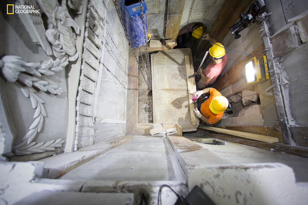Workers begin removing the worn marble that has encased the original burial shelf for centuries, exposing a layer of fill material below. (Dusan Vranic/National Geographic)