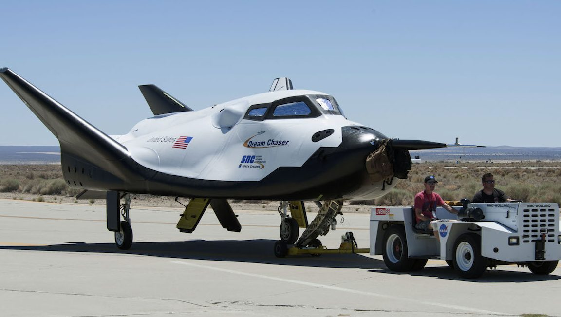 In this June 27, 2013 photo provided by NASA, Sierra Nevada Corp. engineers and technicians prepare the Dream Chaser engineering test vehicle for tow tests at NASA's Dryden Flight Research Center in California. On Thursday, Jan. 14, 2016, NASA announced the Sierra Nevada Corp. will join SpaceX and Orbital ATK in launching cargo to the International Space Station. These flights, yet to be finalized, will run through 2024. (Ken Ulbrich/NASA via AP)