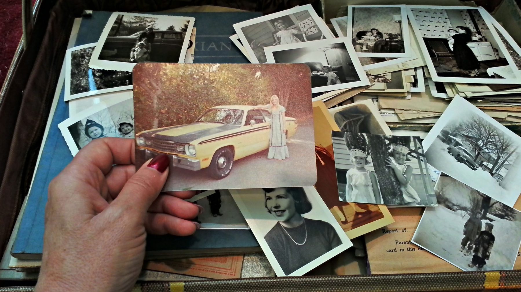 A woman is looking through a trunk of old photos.  (Getty Images)