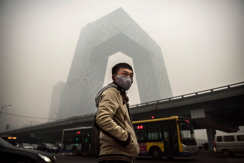 A Chinese man wears a mask as he waits to cross the road near the CCTV building during heavy smog on November 29, 2014 in Beijing, China. United States President Barack Obama and China's president Xi Jinping agreed on a plan to limit carbon emissions by their countries, which are the world's two biggest polluters, at a summit in Beijing earlier this month. (Kevin Frayer/Getty Images)