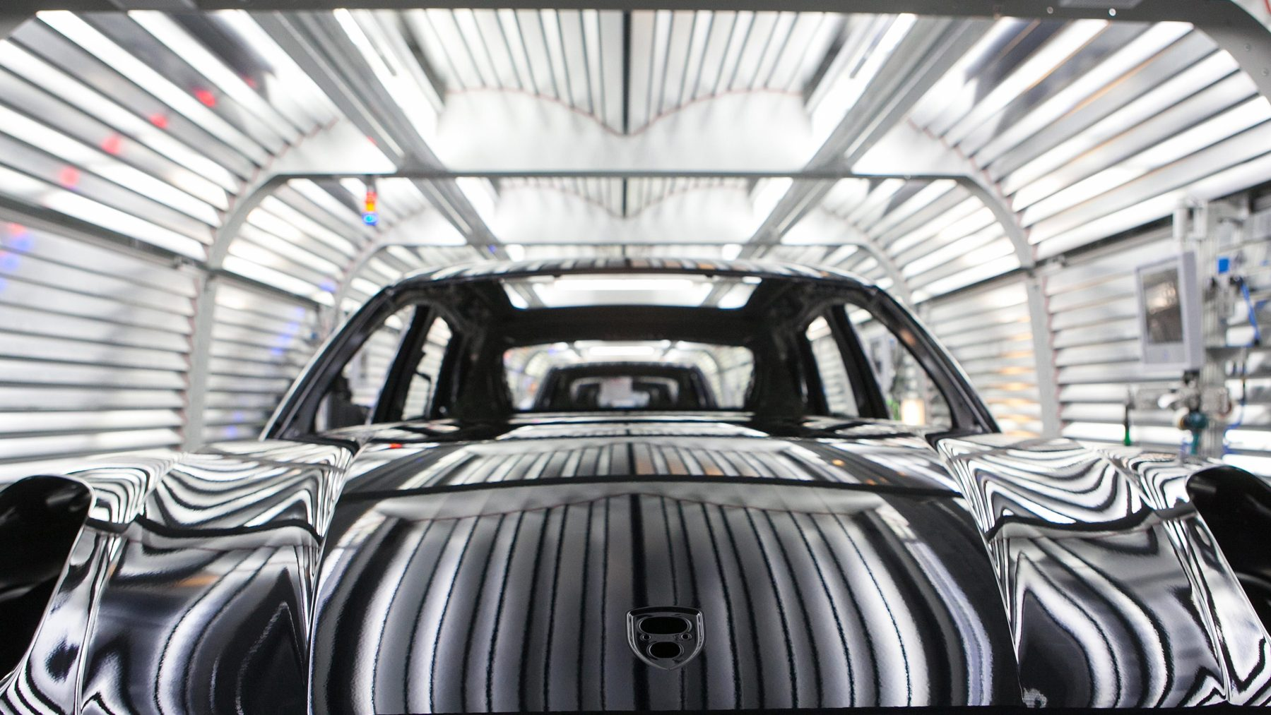 Painted chassis of Porsche Macan sport-utility vehicles (SUV) pass through the paint shop inside the newly expanded Porsche AG factory in Leipzig, Germany, on Wednesday, Feb. 5, 2014. Porsche AG Chief Executive Officer Matthias Mueller said the high-end automaker will exceed 200,000 in annual deliveries in 2015, three years earlier than first targeted, on demand for the Macan compact sport-utility vehicle going on sale later this year. (Krisztian Bocsi/Bloomberg via Getty Images)