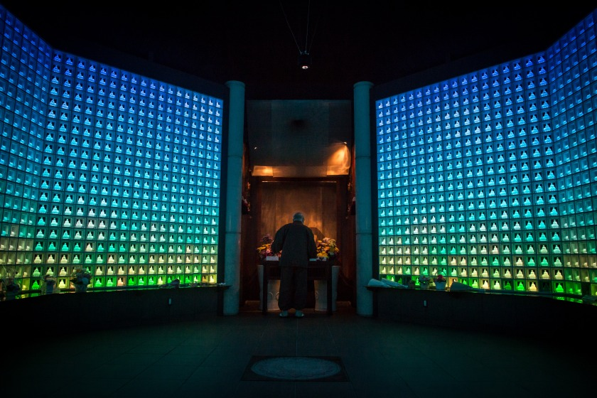 Koukokuji temple head priest Yajima Taijun demonstrates a prayer ritual inside the Ruriden columbarium as glass Buddha alters are lit up on April 6, 2015 in Tokyo, Japan. The Ruriden, operated by the Koukokuji buddhist temple, took two years to build and houses 2046 futuristic alters with glass buddha statues that correspond to drawers storing the ashes of the deceased. An IC card allows the owner of the alter to access the building and lights up the corresponding statue. The ashes are stored for 33 years before being buried below the Ruriden, currently 600 alters are in use and another 300 are reserved. (Photo by Chris McGrath/Getty Images)