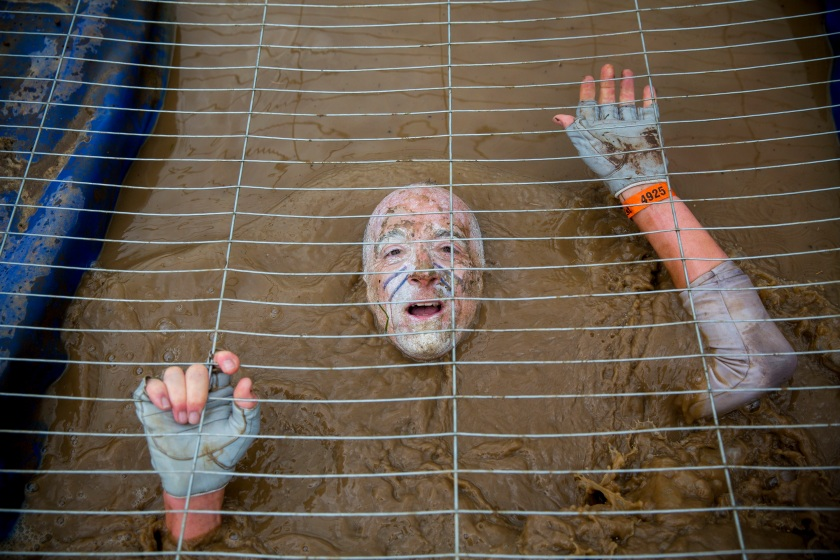 Competitors crawl in a cage filled with muddy water while challenging in Tough Mudder endurance race in Henley-on-Thames, England on 27 April, 2014. (Tolga Akmen/Anadolu Agency/Getty Images)