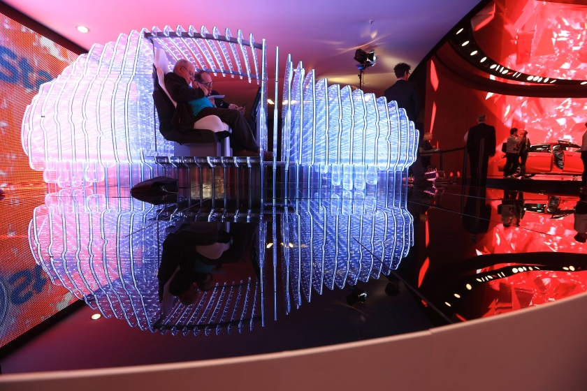 Visitors sit inside a light installation in the shape of a car on the Opel OnStar display, Adam Opel AG's in-car connected app technology, on the company's stand during previews to IAA Frankfurt Motor Show in Frankfurt, Germany, on Tuesday, Sept. 15, 2015. (Krisztian Bocsi/Bloomberg via Getty Images)